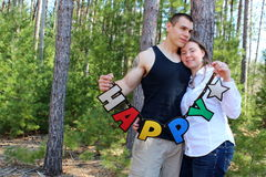 Young couple holding up sign that reads 'happy' Stock Image