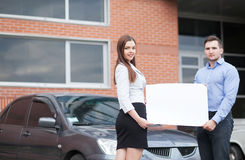Young couple holding a white sheet on a background of the car Stock Photography