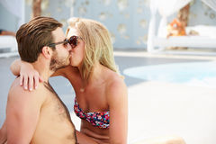 Young Couple On Holiday Relaxing By Swimming Pool Stock Photography