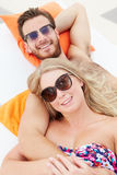 Young Couple On Holiday Relaxing By Swimming Pool Royalty Free Stock Photos