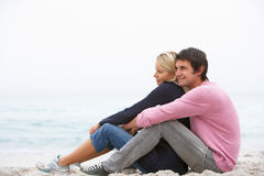Young Couple On Holiday Sitting On Winter Beach. Hugging Stock Photography