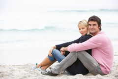 Young Couple On Holiday Sitting On Winter Beach. Smiling At Camera Royalty Free Stock Images