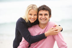 Young Couple On Holiday Sitting On Winter Beach. Smiling At Camera Royalty Free Stock Photos