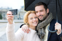 Young couple on holidays under the rain taking selfie Stock Photos