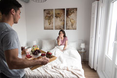 Young couple at home with breakfast in bed suprise.  Royalty Free Stock Photography
