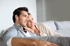 Young couple at home on couch Stock Photos