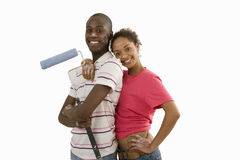 Young couple home decorating, man with paint roller, woman embracing man, smiling, portrait, cut out. Young couple home decorating, men with paint roller, women stock photography
