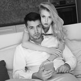 Young couple at home. Handsome brunette men sitting at sofa and using smartphone. Pretty beautiful caucasian girl with bllonde hair standing from the back and Stock Photo
