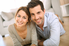 Young couple at home lying on floor Stock Photos