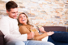 Young couple at home, smiling. Young couple at home with wine, smiling at each ohter royalty free stock photo
