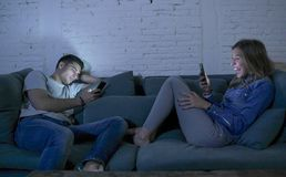 Young couple at home sofa couch smiling happy together but separated ignoring each other concentrated on mobile phone in internet stock photo