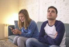 Young couple at home sofa couch with woman internet and mobile phone addiction ignoring her boyfriend feeling sad jealous frustrat royalty free stock photos