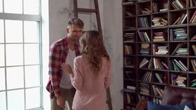 Young couple at home together saint valentine`s day concept at library playing with each other. Young couple at home together saint valentine`s day in the stock video footage