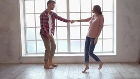 Young couple at home together saint Valentine`s Day concept near window dancing playful. Young couple at home together saint Valentine`s Day near the window stock video
