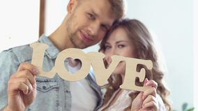 Young couple at home together saint Valentine`s Day concept near window showing love sign. Young couple at home together saint Valentine`s Day near the window stock video footage
