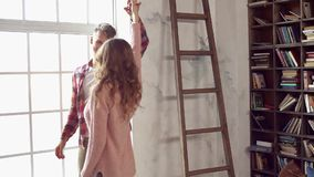Young couple at home together saint valentine`s day concept at library dancing. Young couple at home together saint valentine`s day in the library dancing moving stock footage