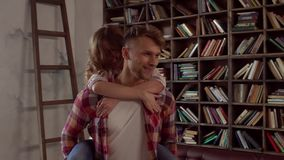 Young couple at home together saint valentine`s day concept at library guy carry girlfriend. Young couple at home together saint valentine`s day in the library stock video footage