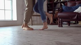 Young couple at home together saint valentine`s day concept at library near the window legs close-up. Young couple at home together saint valentine`s day in the stock video footage