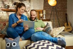 Young couple at home using tablet Stock Photo