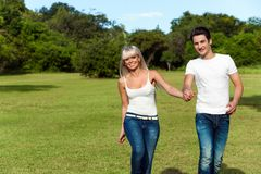 Young couple hopping together in park. Stock Photography