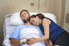 Young couple at hospital room man lying in bed worried woman holding his hand caring Stock Images