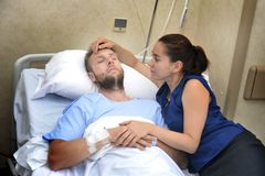 Young couple at hospital room man lying in bed worried woman holding his hand caring Royalty Free Stock Images