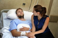 Young couple at hospital room man lying in bed worried woman holding his hand caring. Young sick men lying in bed at hospital room after suffering accident Stock Image