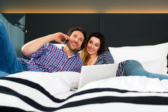 Young couple in Hotel in bed with phone and computer Royalty Free Stock Image