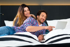 Young couple in Hotel in bed with wifi and computer Stock Photography