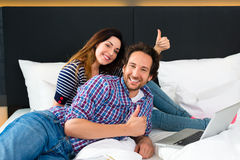 Young couple in Hotel in bed with wifi and computer Royalty Free Stock Images