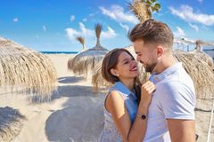 Young couple hug in a beach with parasol. At summer Royalty Free Stock Photo