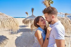 Young couple hug in a beach with parasol. At summer Royalty Free Stock Image