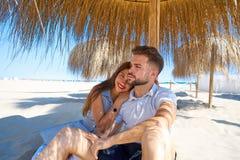 Young couple hug in a beach under parasol Royalty Free Stock Photos