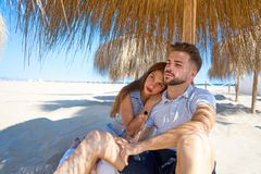 Young couple hug in a beach under parasol. At summer Royalty Free Stock Photo