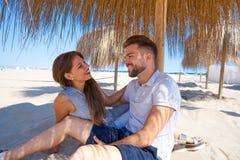 Young couple hug in a beach under parasol Stock Photos