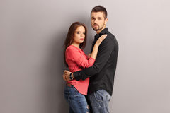 Young couple hugging against a gray wall Stock Image