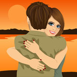 Young couple hugging on bank of river in evening at sunset Stock Photos