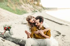 A young couple is hugging on the beach. Beautiful girl embrace her boyfriend from back. Wedding walk. A newlyweds looks. At each other. Artwork, soft focus Stock Photos