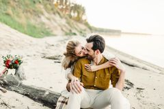 A young couple is hugging on the beach. Beautiful girl embrace her boyfriend from back. Wedding walk. A newlyweds looks. At each other. Artwork, soft focus Stock Photo