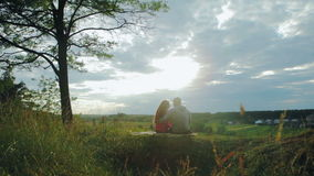 Young couple hugging in the field and looking at stock video