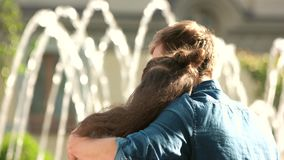 Young couple hugging at fountain, back view. stock video