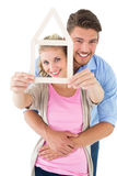 Young couple hugging and holding house outline Royalty Free Stock Photography