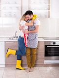 Young couple hugging after housework. Happy young couple hugging in kitchen after housework is done Stock Photography