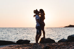 Young couple hugging and kissing on a beach. In sunset Stock Images