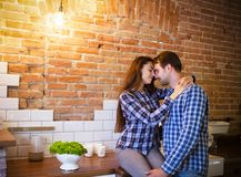 Young couple hugging and kissing at kitchen. Love and passion concept Stock Image