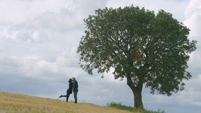 Young couple hugging and kissing under big green tree, eternal love forever stock video footage
