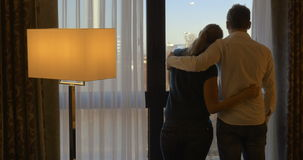Young couple hugging and looking out the window stock footage