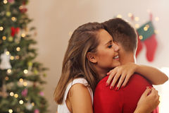 Young couple hugging over Christmas tree Stock Photography