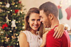 Young couple hugging over Christmas tree Royalty Free Stock Photography