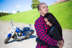 Young couple hugging on road with retro motorcycle Royalty Free Stock Photos